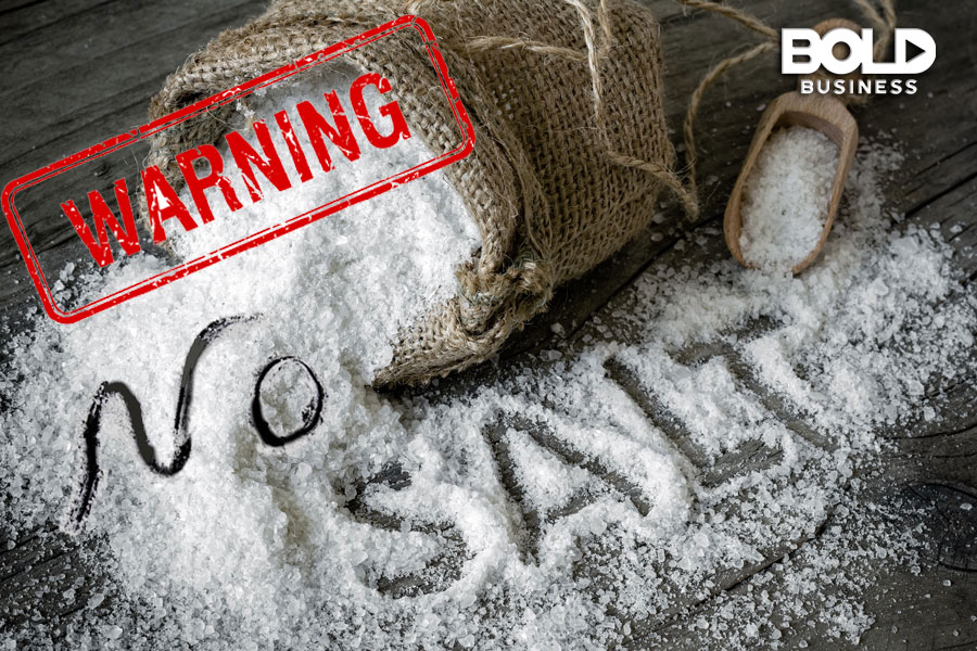 "a photo of spilled salt on a table top with the words ""No Salt"" engraved on the scattered salt and a stamped word ""WARNING"" near the bag from where the salt spills amid the availability of heart-healthy cooking classes"
