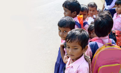a group of children wearing backpacks and school uniforms - a picture of barriers to education