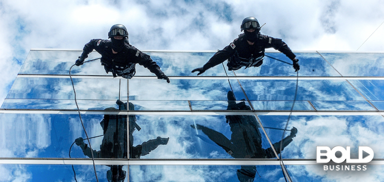 a photo of two soldiers rappelling down the side of a glass building as an example challenge that's done during Contested Urban Environment meetings