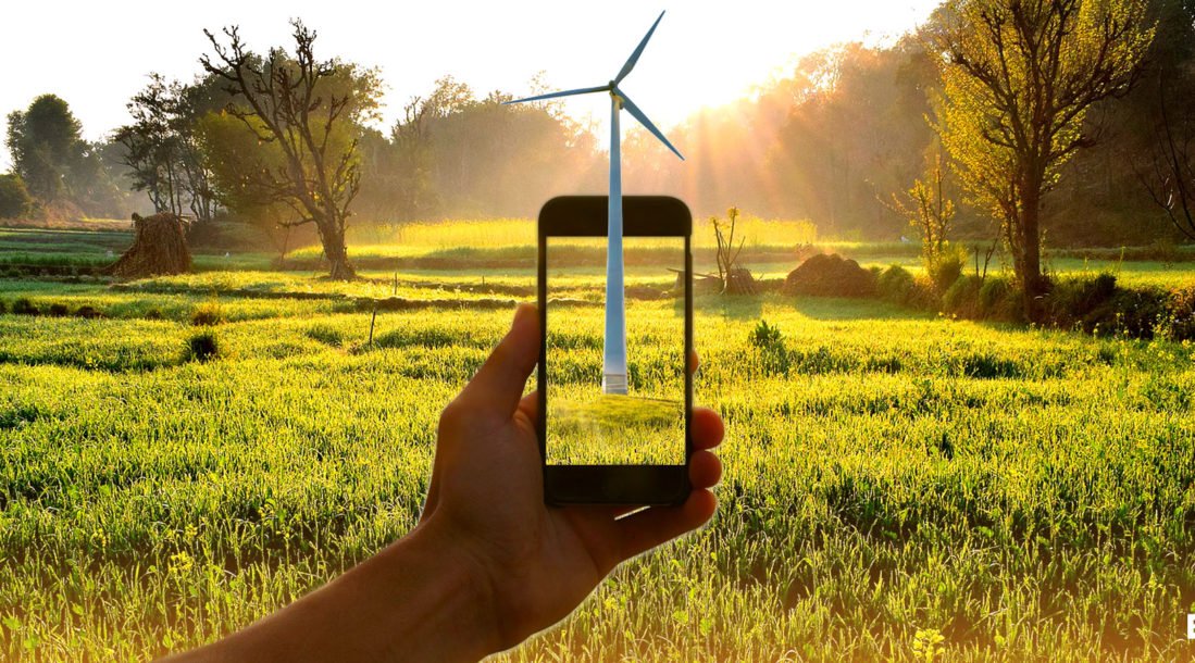 a photo of a cell phone held up in a background of green field with a green field showing on its screen as well amid the existence of the T-Mobile sustainability plan