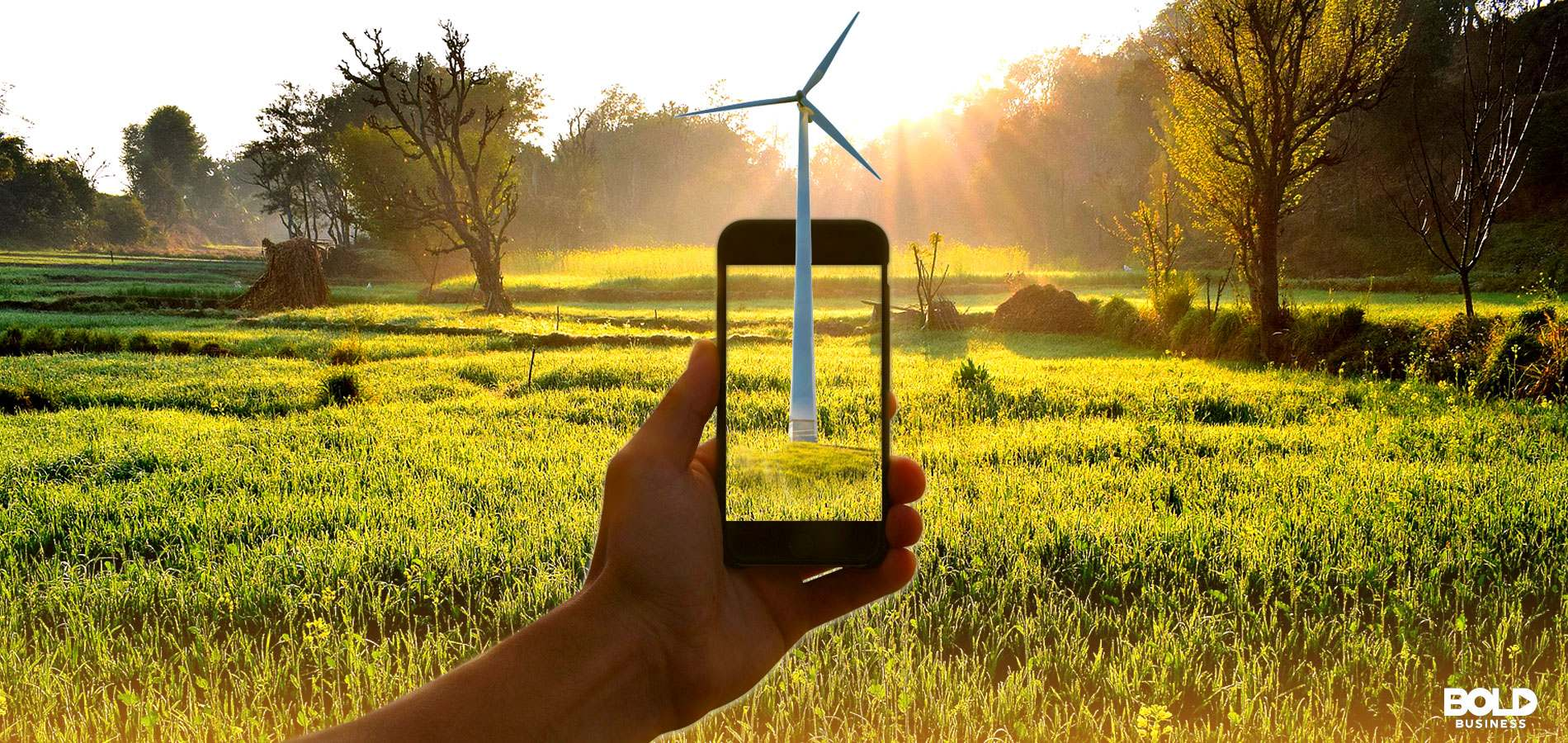 A cell phone held up in a green space with green space on its screen as well