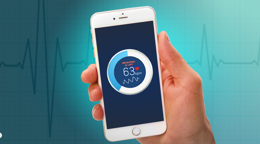 a photo of a hand holding a phone with its screen open, showing the iPhone heart rate monitor app