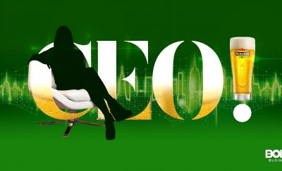 Heineken green backdrop with 'CEO' and silhouette of woman professional sitting in desk chair
