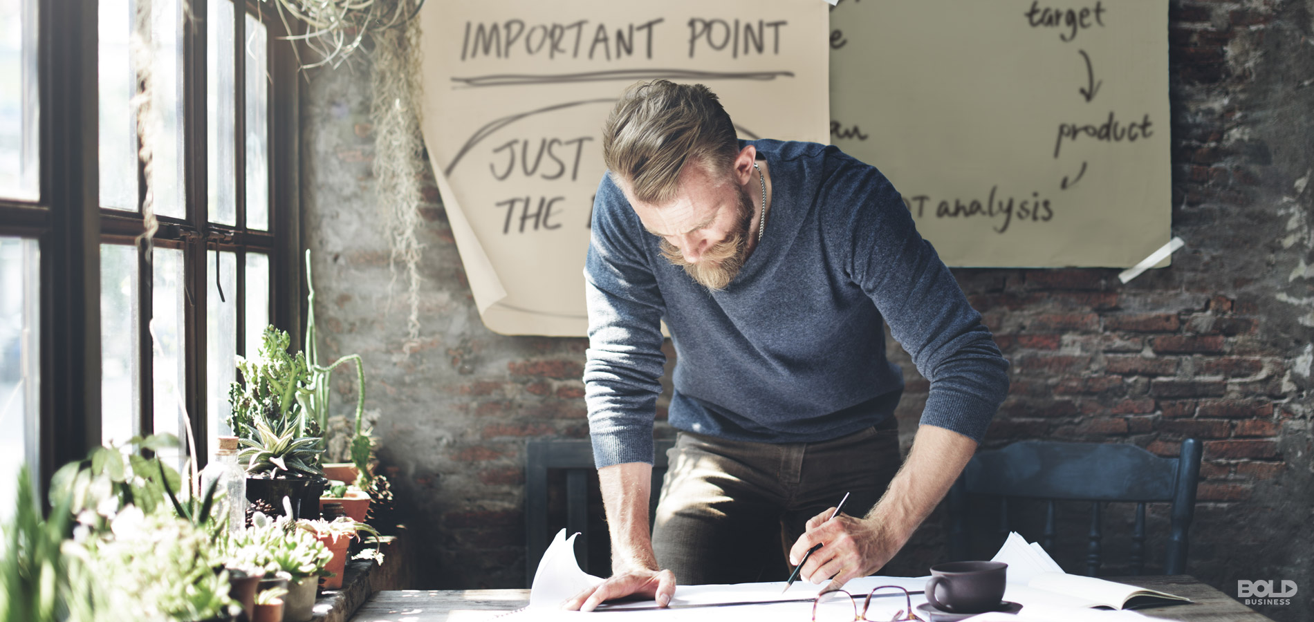 man in blue shirt standing up behind a desk writing