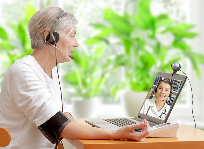 elderly woman using blood pressure monitor while teleconferencing with her doctor