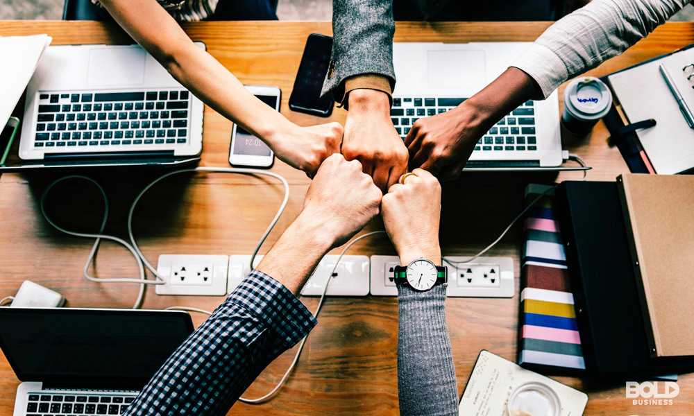 a team of five doing a fist bump over an office table showing competitive market dynamics