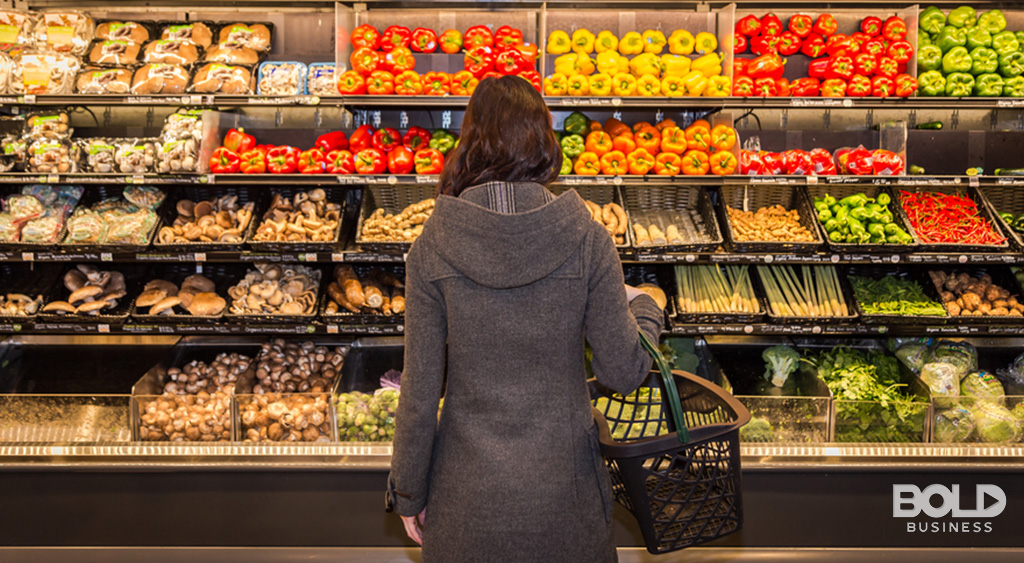a woman standing in front of the fruits and vegetables section