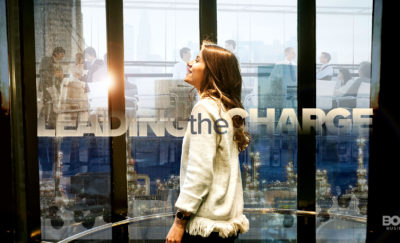 a photo of a woman standing inside an elevator and looking up amidst a collection of photos of Women in the C-suite working