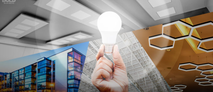 A hand holding a light bulb which shines on the road to innovative and smart cities brought about by the Evolution of Lighting