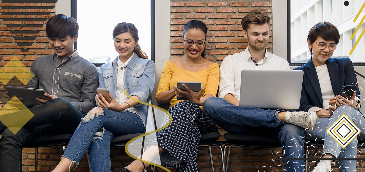 Three women and two men leaning against a wall while seated and smiling at their electronic gadgets amidst the fact that Millennials in the Workplace are Shaping Businesses and Leadership