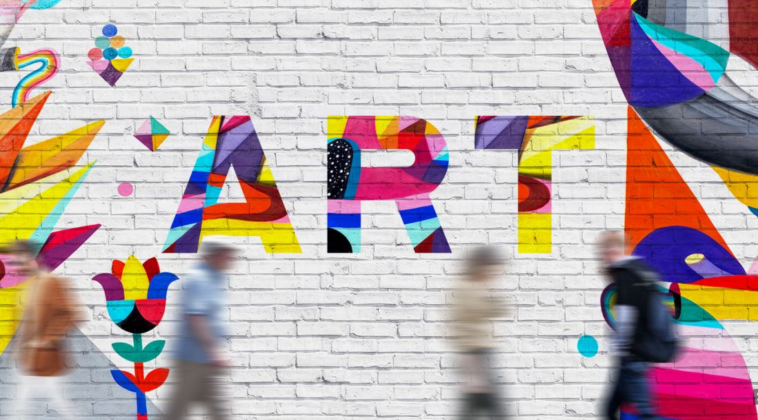 "A photo of the word ""ART"" in different colors set on a gray brick wall reflecting - Art and Its Impact on Society: Art Districts Revitalizing Communities"