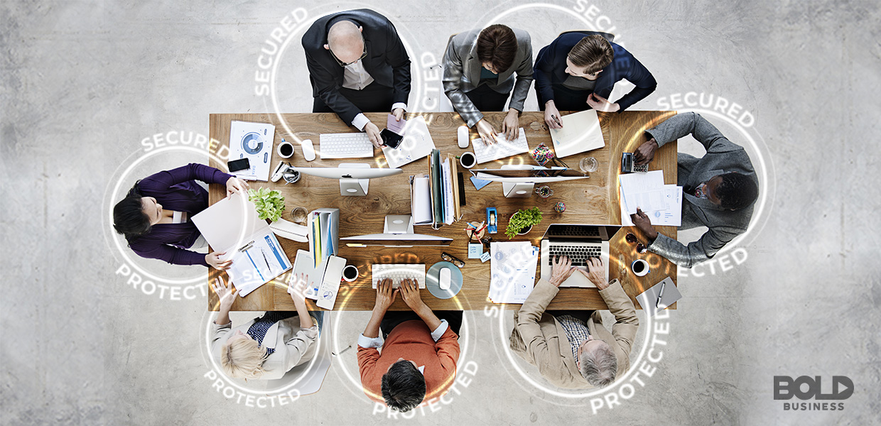 An aerial view of a business people working on their laptops while seated around a table amidst the emergence of Leaders in Cybersecurity