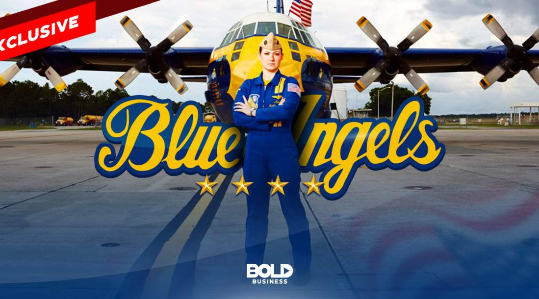 Katie Higgins Cook in her Blue Angel suit standing in front of an aircraft