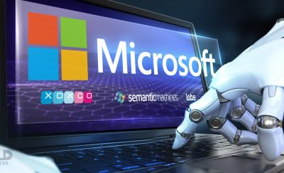 A photo of a robot hand typing on a laptop keyboard with the logo of Microsoft on the screen amidst Microsoft's recent acquisitions
