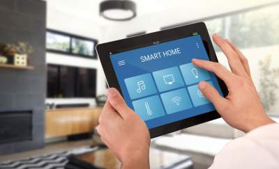 a photo of a pair of hands holding up an iPod which has buttons that control the various smart appliances (included in a smart home entertainment system) in the background