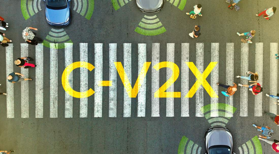 a photo of an aerial view of a pedestrian lane where people are crossing a street with cars stopped on both lanes while there are current innovations in transport systems like V2X technology in the world