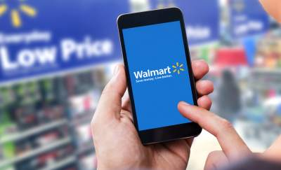 Walmart technology strategy, hand holding a smart phone with walmart logo on screen