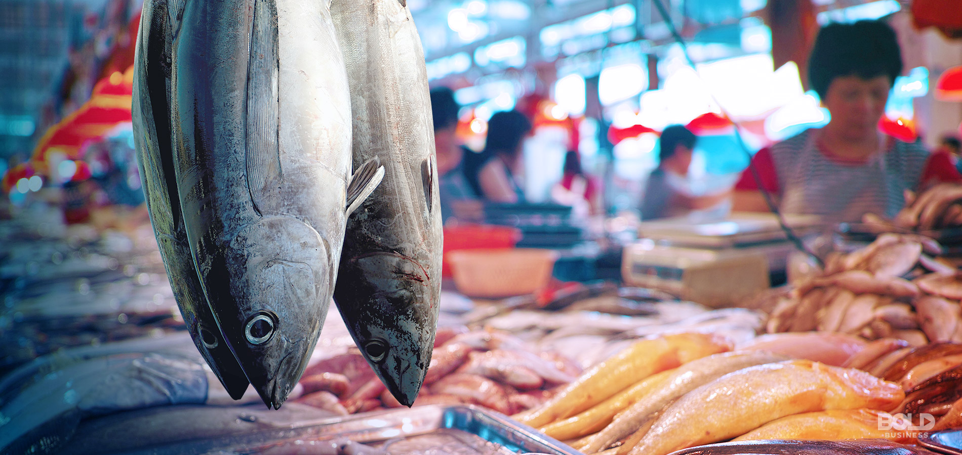 a photo of a couple of fresh fish hanging from a wet market stall in front of a background of market sellers busy with selling their fish amid the rise of aquaculture and fisheries
