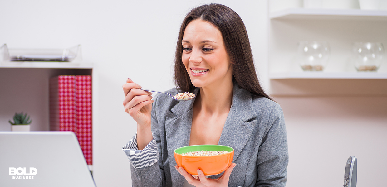 a photo of a woman seated at her desk eating oatmeal from an orange bowl while looking at her laptop screen, showing that quick and healthy breakfast alternatives are on the rise