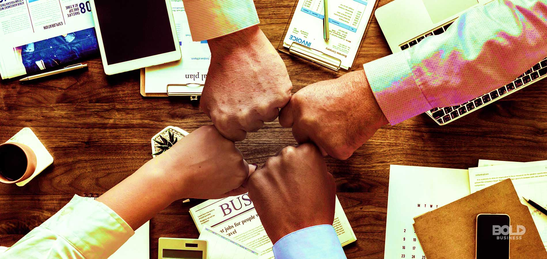 a photo of four hands making a fist bump on top of a table full of documents and office materials amidst the rise of top chief marketing officers in the world