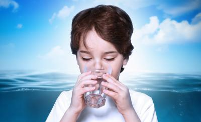 water desalination, child drinking water with the ocean as background