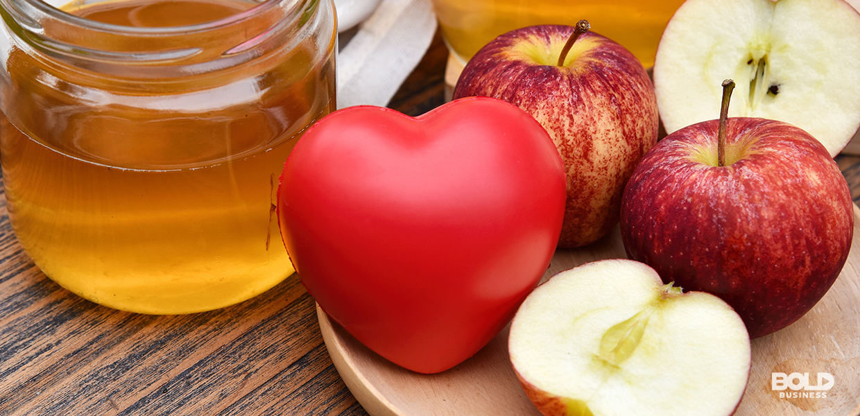 a photo of a rubber heart beside apples and a jar of honey amid the ongoing research about the question of whether probiotics lower cholesterol levels or not