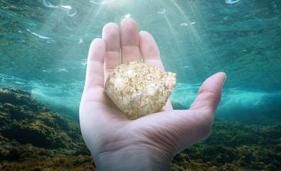 ocean minerals, hand holding a mineral underwater