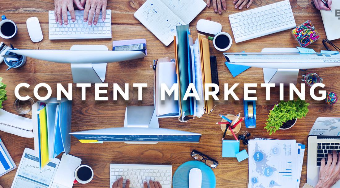a photo of an aerial view of a cluttered rectangular work desk of a group of employees with the word CONTENT MARKETING floating over it