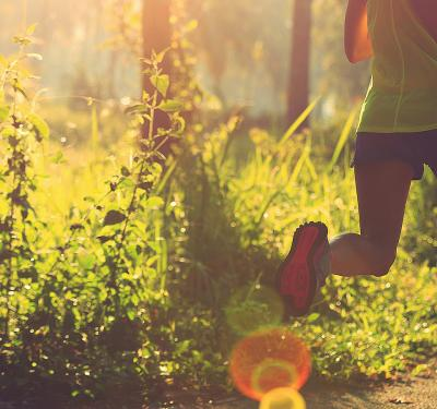 a photo of a woman running on a paved path through a forest as part of her decision in living a healthy lifestyle