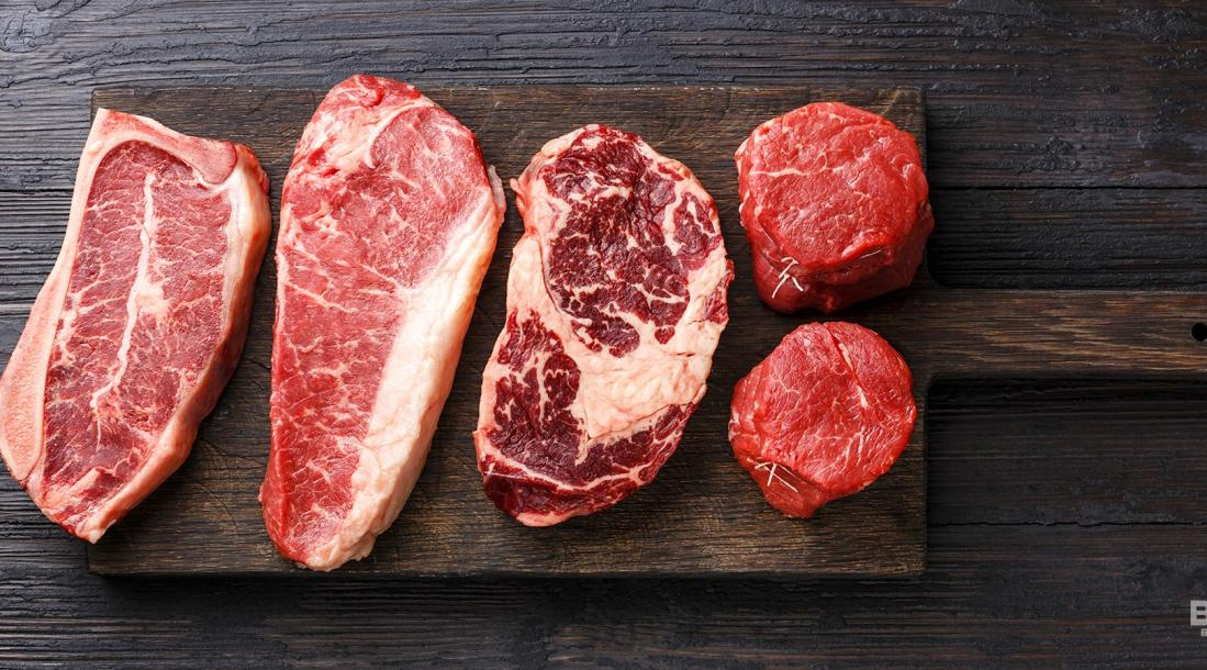 a photo of slabs of different meats on a wooden chopping board amid the rising technologies and solutions from the sector of artificial meat or lab-grown meat