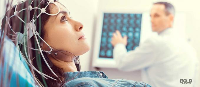 a photo of a doctor with a machine and a woman undergoing non-invasive electroceuticals as treatment for her traumatic brain injury