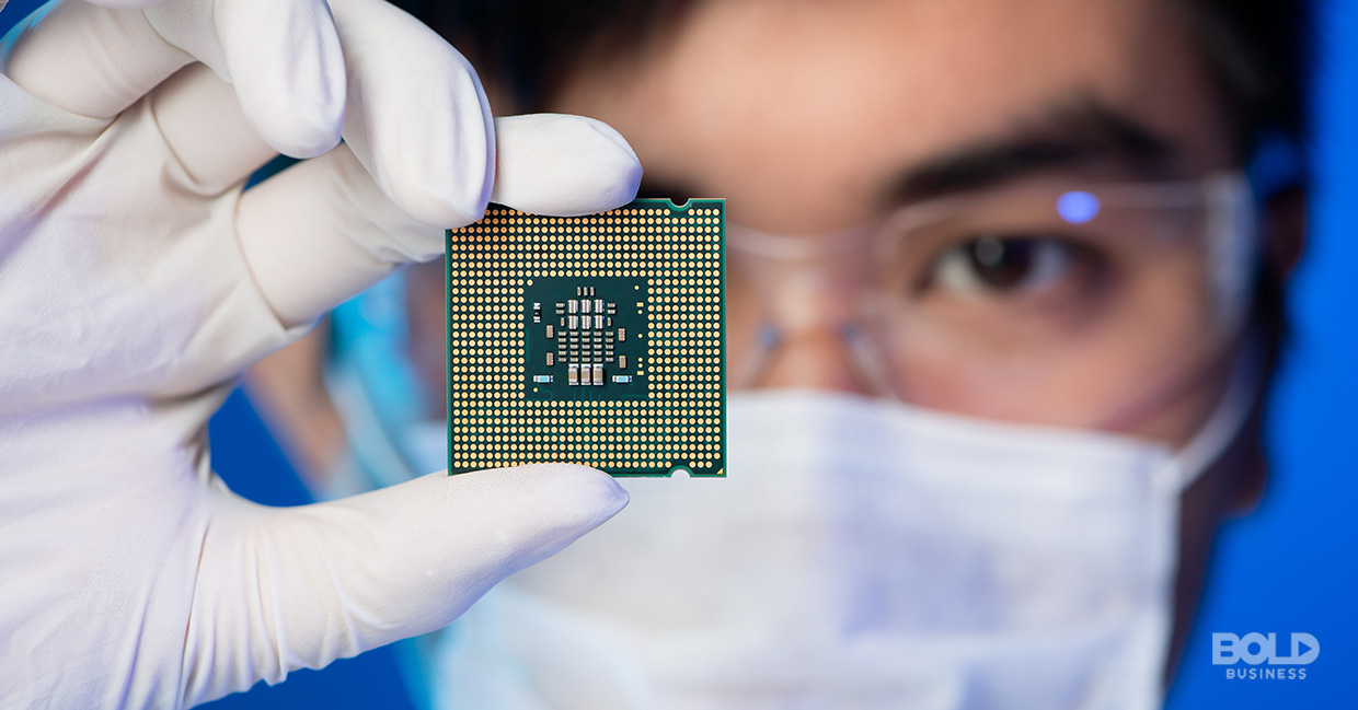 a photo of a semiconductor industry engineer holding up a tiny chip used in material science and engineering