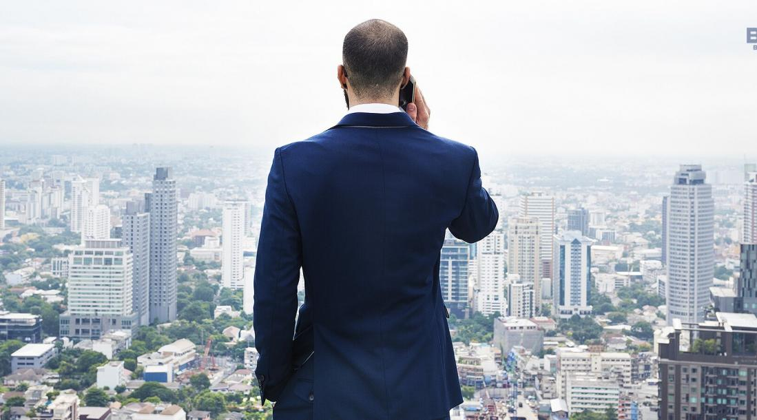 best cities to start a business, man on his back facing a cityscape holding a phone to his ear