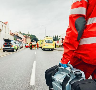 a photo of an emergency responder holding one of the available blood and fluid warming systems of QinFlow as he walks on a road leading to the scene of emergency