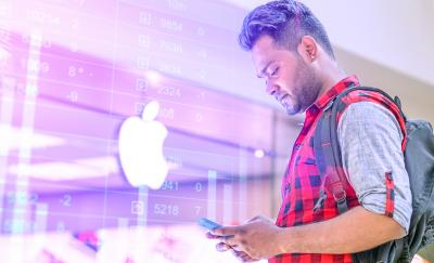 a photo of a man looking down at his phone while standing outside a building with an Apple logo shown visibly at the center, thus depicting discussions on the hot topic of Apple apps and the Apple App Store