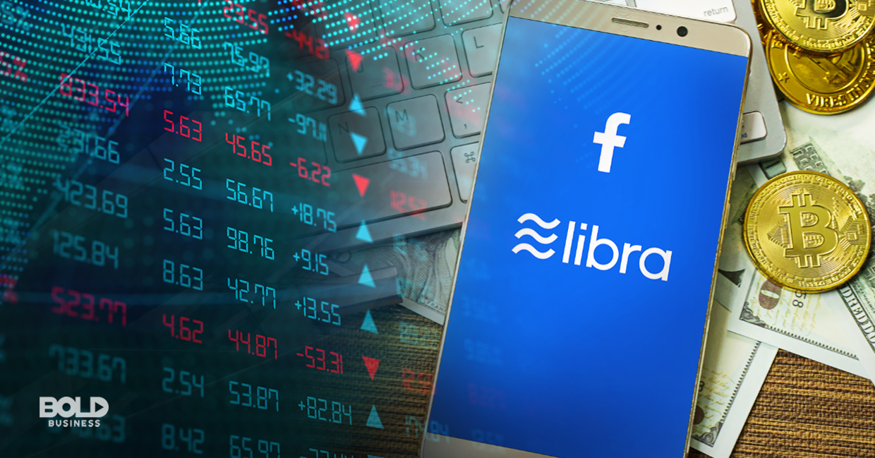 a photo of a phone with its screen open to a digital page showing Facebook's Libra coin logo; the background of the phone is a chart of the stock market figures and a tabletop full of dollar bills and pennies
