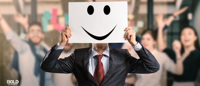 a photo of a man wearing a suit and holding up a white board with a smiley face etched on it, while in front of a blurred photo of a cheering crowd applauding the great employee benefits offered to them