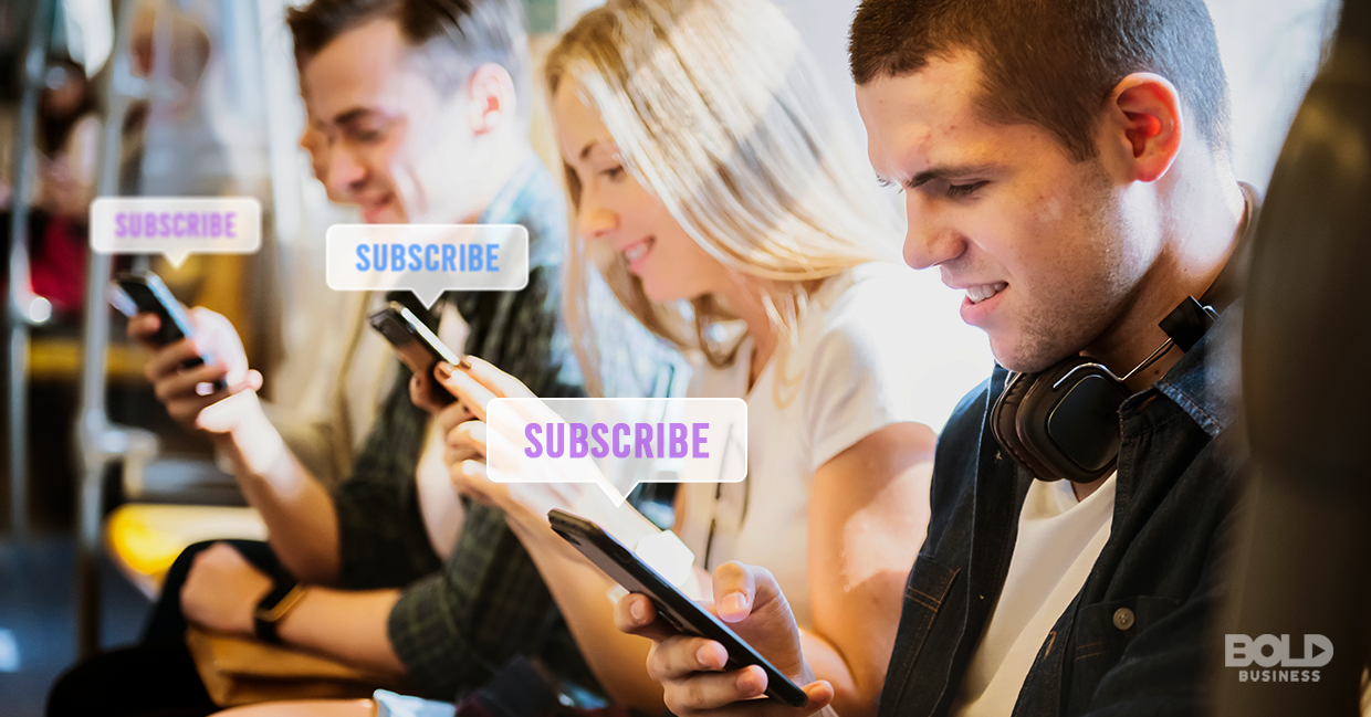 a photo of lined-up sitting young men and women looking and smiling at their phones while hitting the subscribe option on their screens amid the rise of the subscription economy