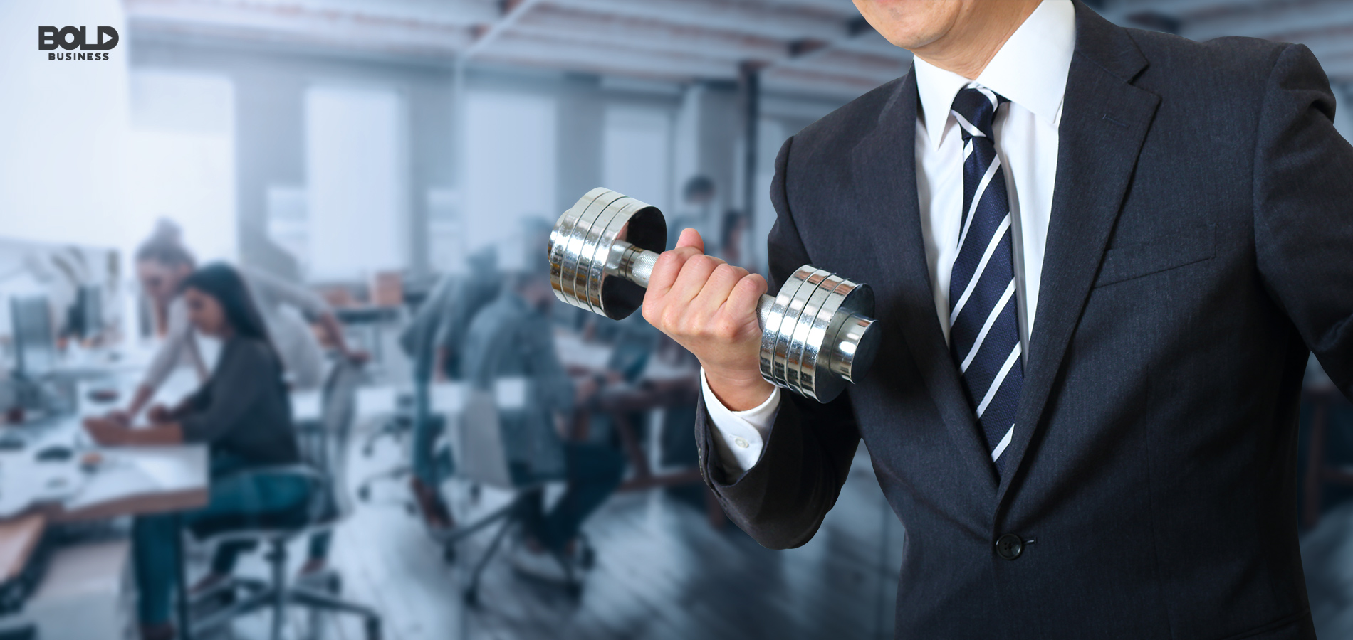 a photo of a suited man lifting a dumbbell amid his working colleagues in a StayWell Company office behind him