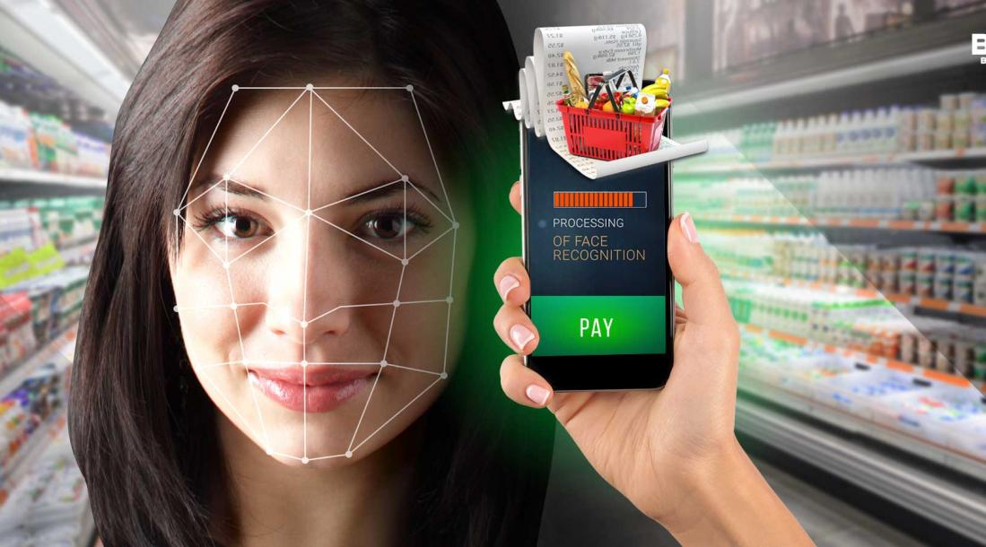 """a photo of a woman's face being scanned with a phone that has its screen showing the words, """"PROCESSING OF FACE RECOGNITION"""" and an image of a grocery basket and receipt, depicting the rising trend of biometric wallets"""