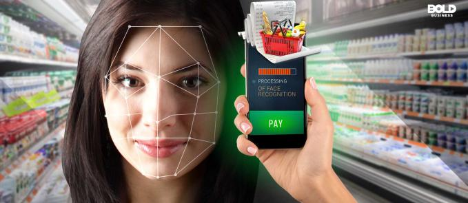 "a photo of a woman's face being scanned with a phone that has its screen showing the words, ""PROCESSING OF FACE RECOGNITION"" and an image of a grocery basket and receipt, depicting the rising trend of biometric wallets"