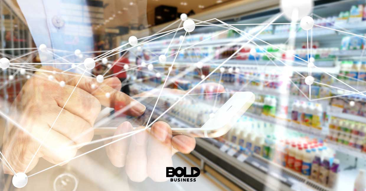 a photo of a grocery aisle and translucent image of a hand holding up a smart phone and the crisscrossing network lines depicting the rise of biometric wallets
