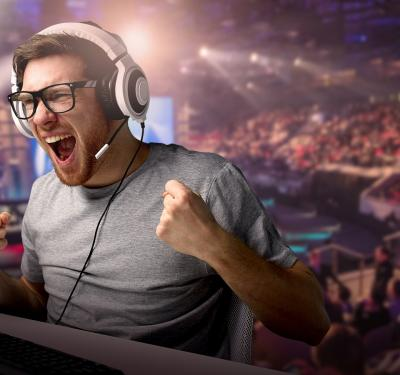 a photo of an esports industry gamer yelling in delight at scoring during a live, real-time esports tournament that's watched by a large audience behind him