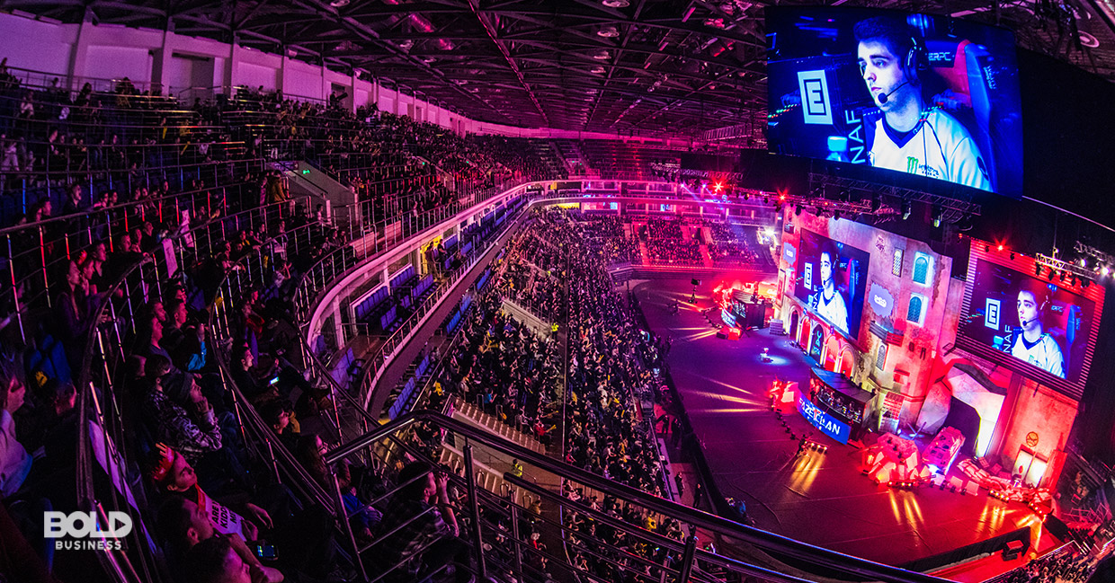 a photo of an esports industry video game tournament with a hall that's full of viewers looking at a huge screen in front with a face of an esports gamer focused on playing the video game in front of him