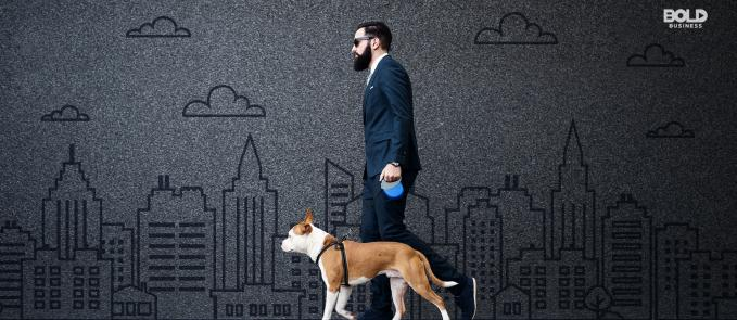 a photo of a man in a business suit walking his dog alongside a wall with a background of an etched city in gray amid the growth of the pet industry
