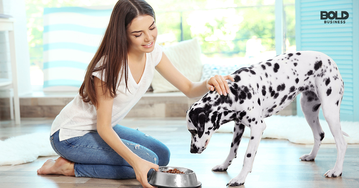a photo of a young woman kneeling on the floor while offering her dalmatian a dog dish filled with dog food amid the growth of the pet industry