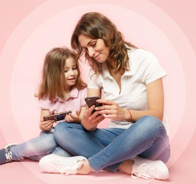 a photo of a mother and a grade-school aged girl looking at their smart phones that has the Bark App installed in them