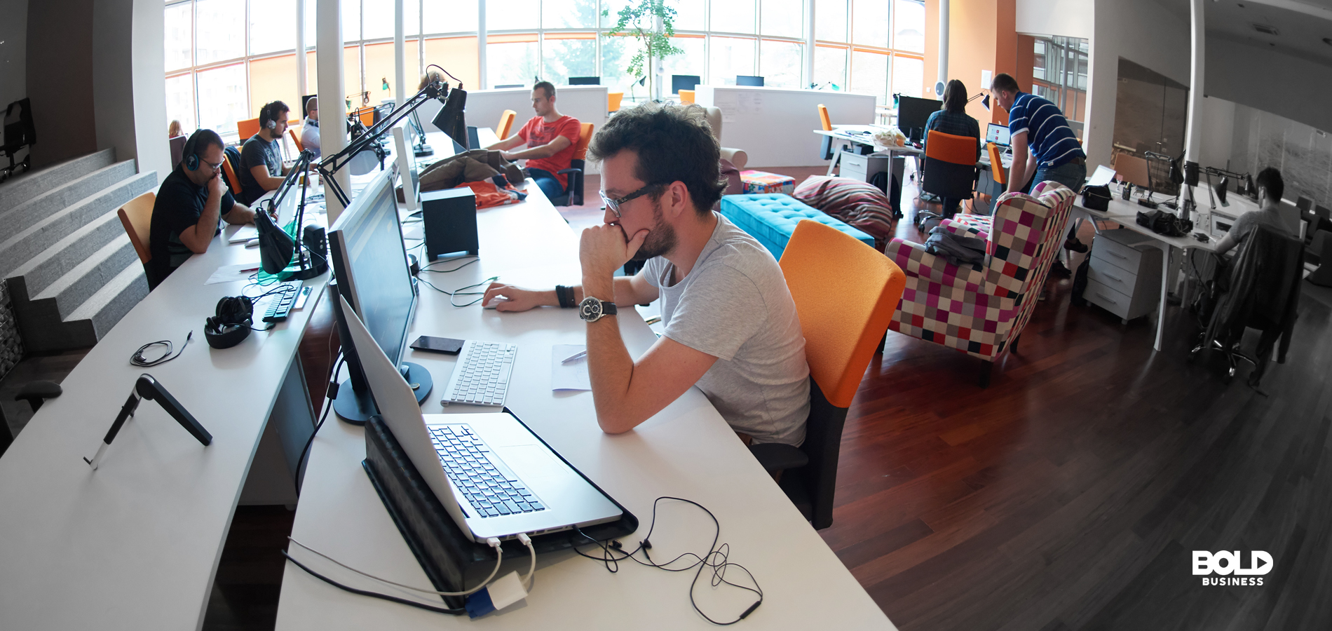 a photo showing a fish-eye view of an open co-working space with startup owners working on their laptops, depicting the possibility of the presence of a startup bubble