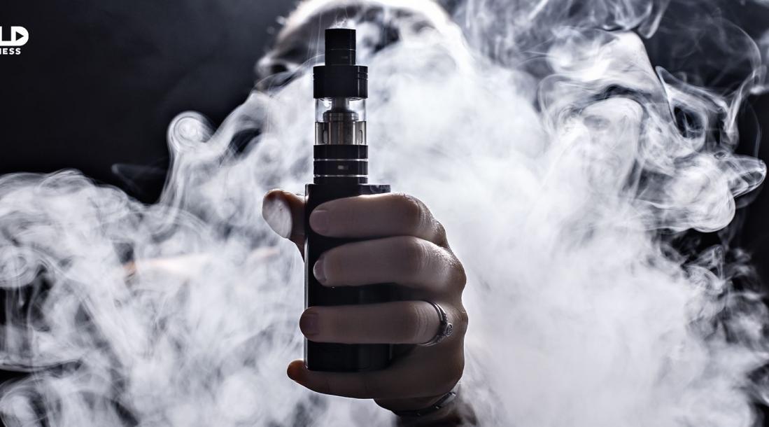 Vaping smoke behind hand holding vape.