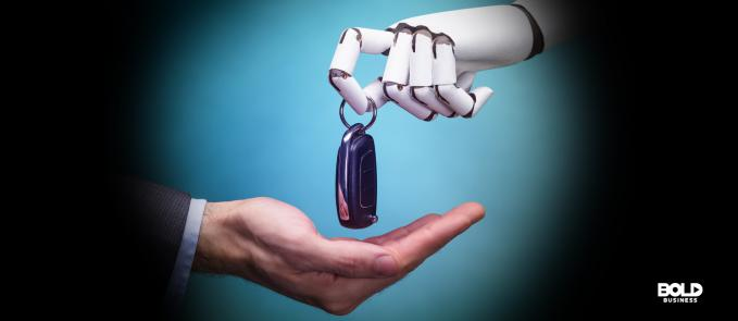 a human hand receiving a car key from a robotic hand, showing an image of progress in automated driving and transportation AI